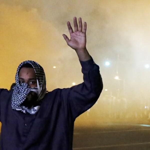 Un residente de Baltimore levanta las manos y se cubre la boca tras permanecer en las calles de Baltimore pese al toque de queda impuesto