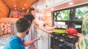 Millennial couple cook breakfast in the van they live in
