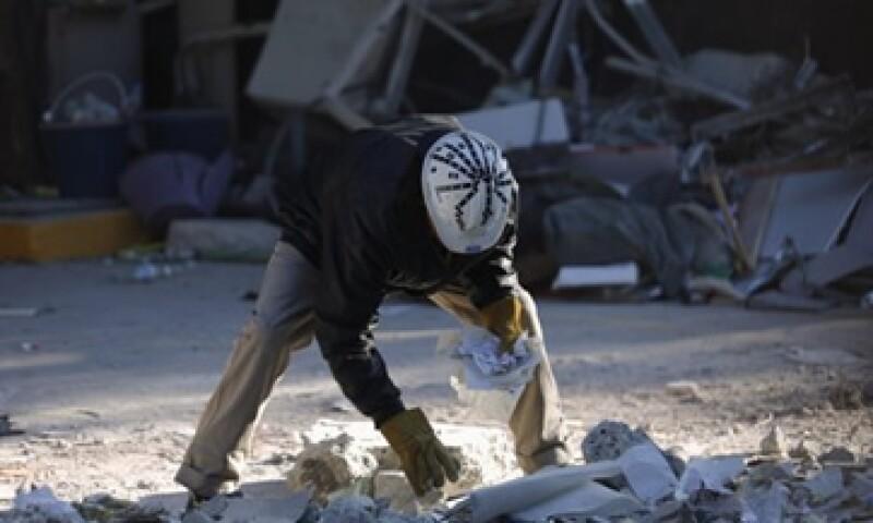 Trabajadores de Pemex reúnen documentos que sobrevivieron a la explosión del jueves. (Foto: Reuters)